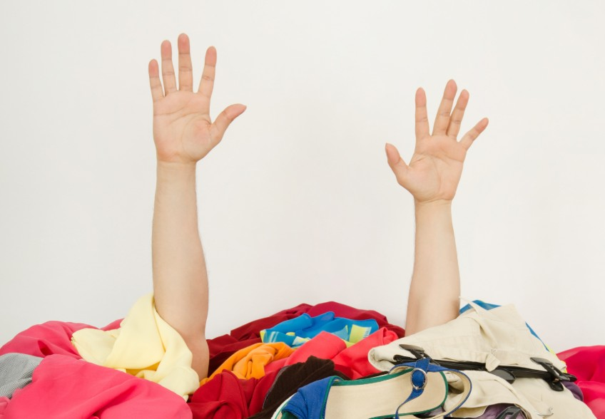 hands reaching out of a pile of clothing