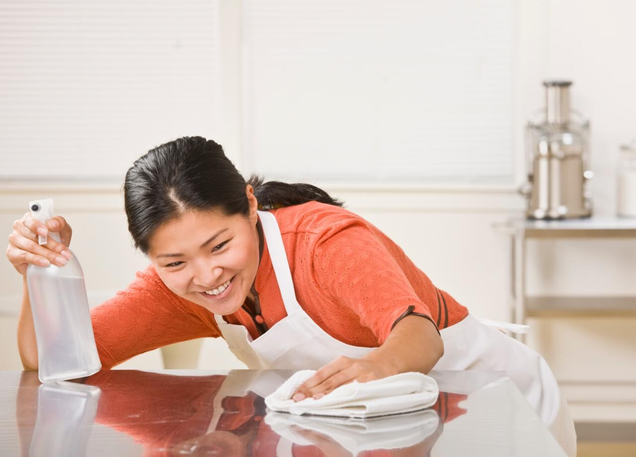 smiling woman cleaning kitchen counter