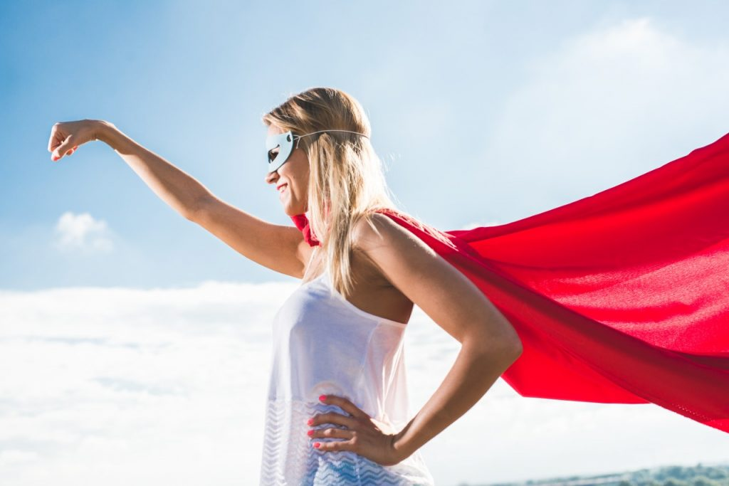 happy woman dressed in superhero cape and mask