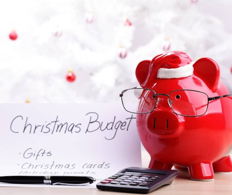 red piggy bank wearing a santa hat and glasses next to a calculator and christmas budget list
