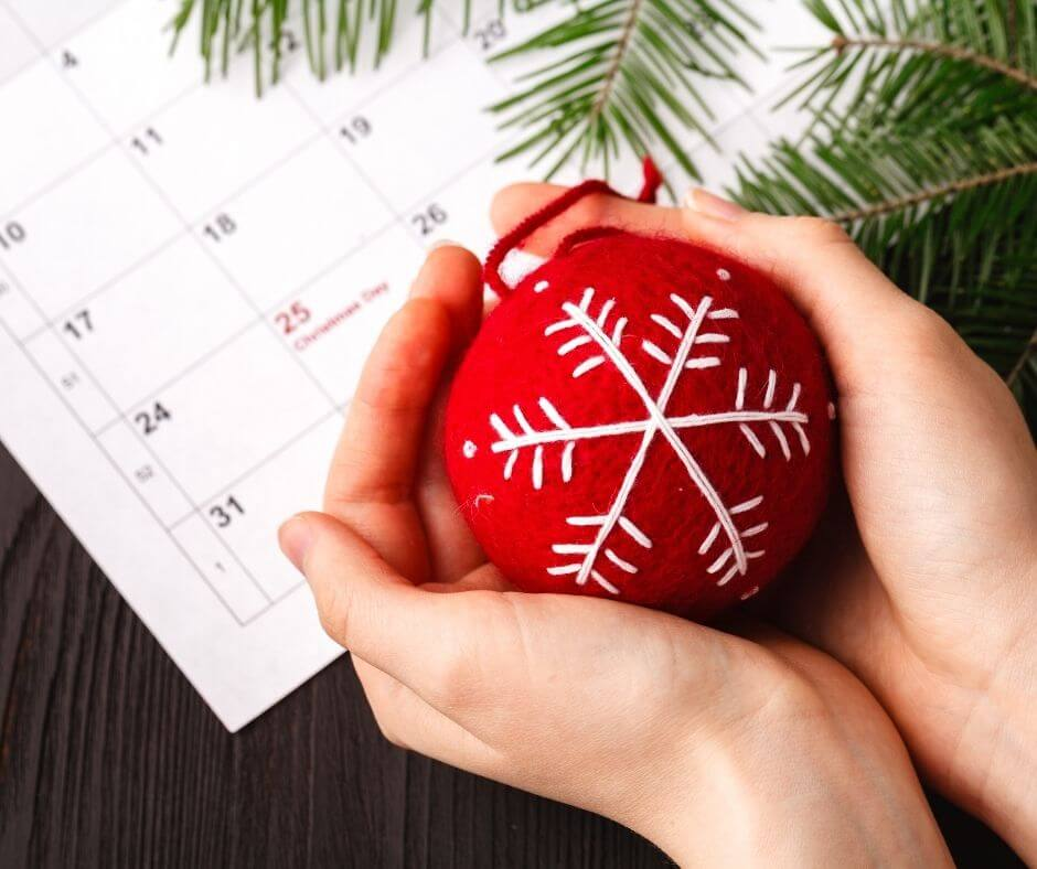 hands holding ornament over a calendar showing christmas day