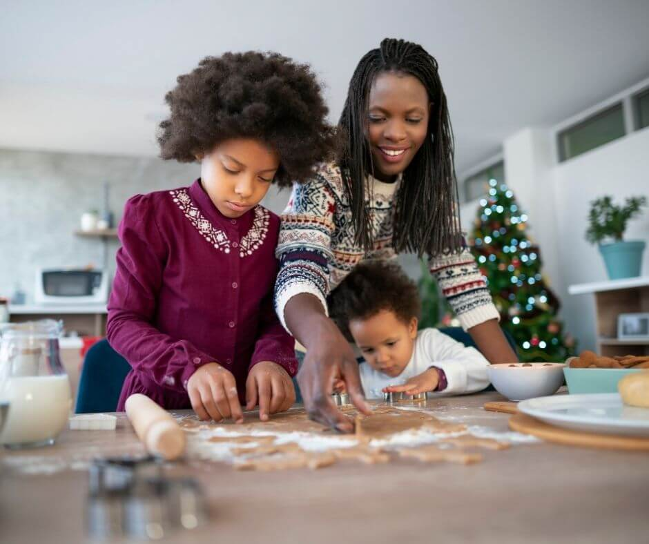 happy black mother and children making christmas cookies together