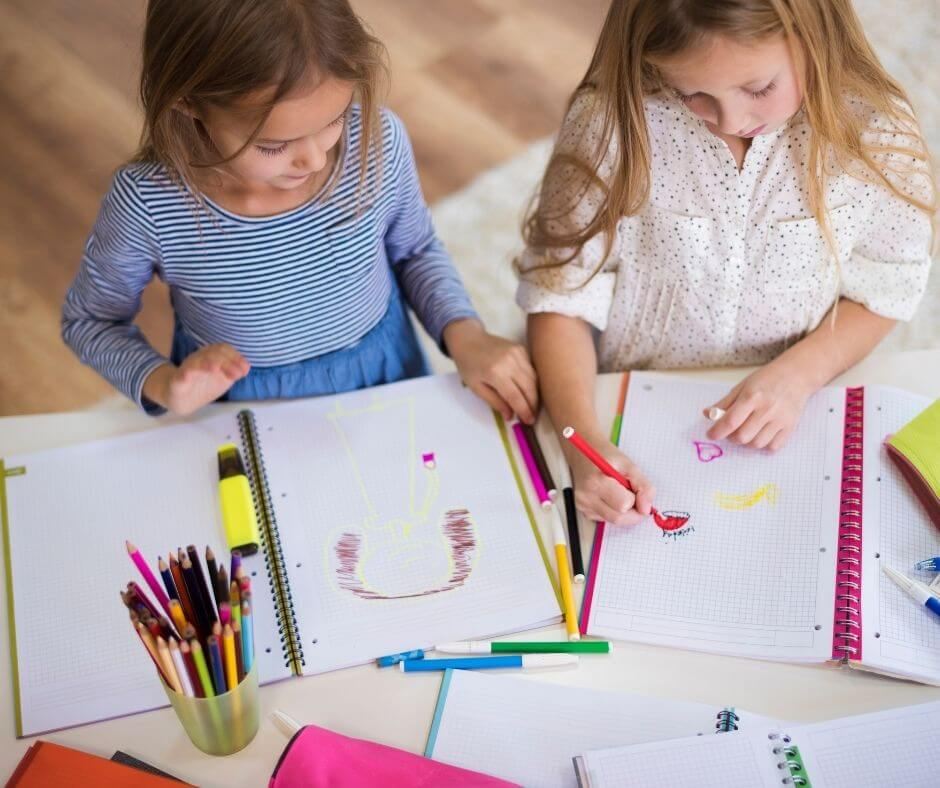 Two girls drawing with markers on notebooks
