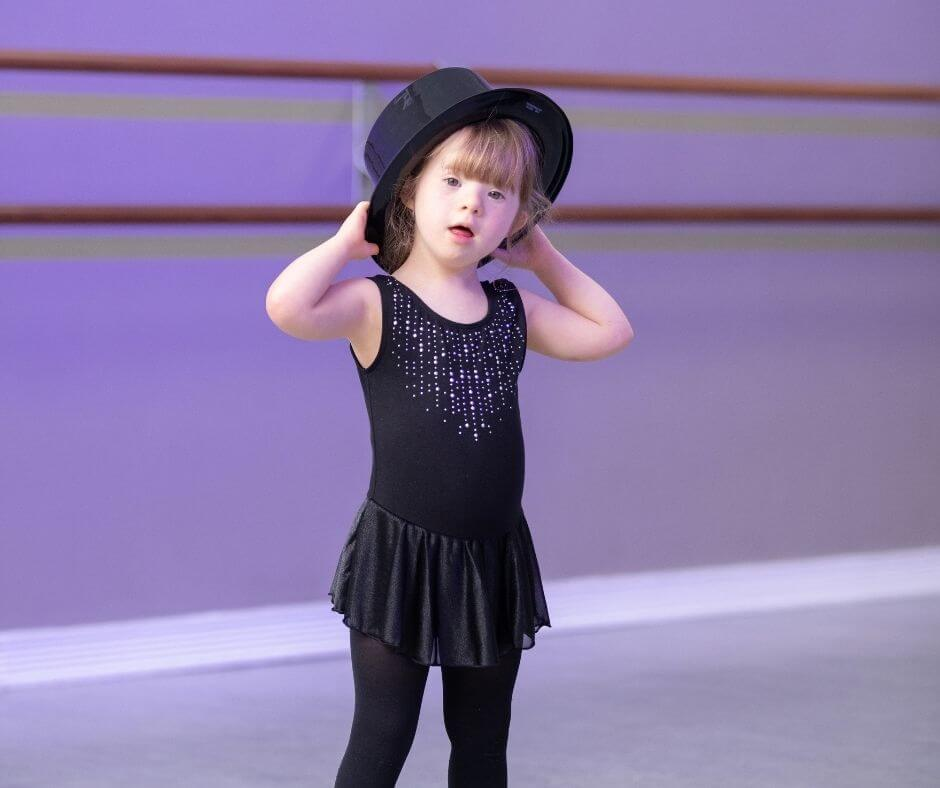 young girl with Downs Syndrome in a jazz dance costume at her dance class