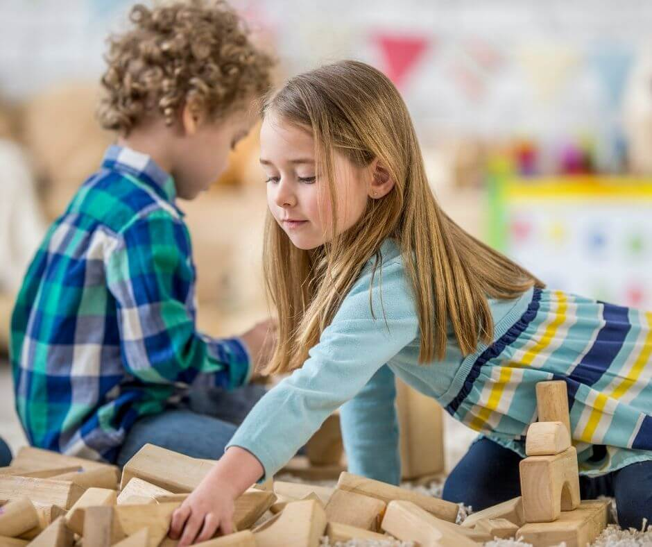 young boy and girl playing with naturl wooden blocks