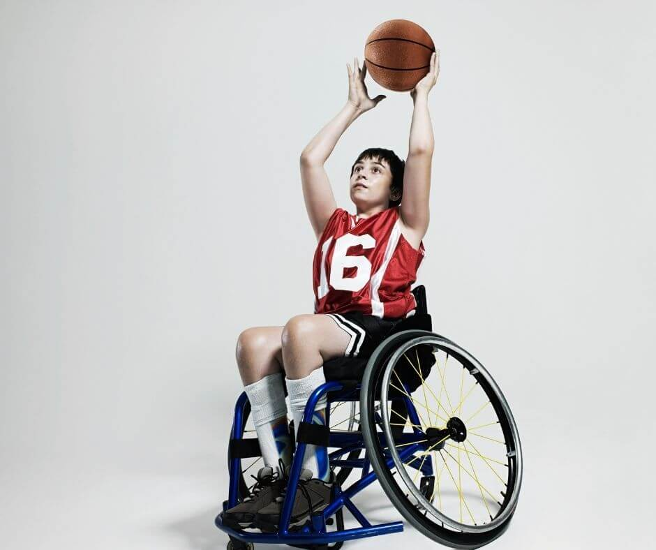 young teenage or preteen boy in a wheelchair, shooting a basketball
