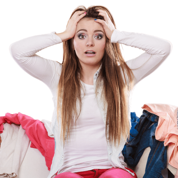 stressed woman sitting on couch surrounded by clothes