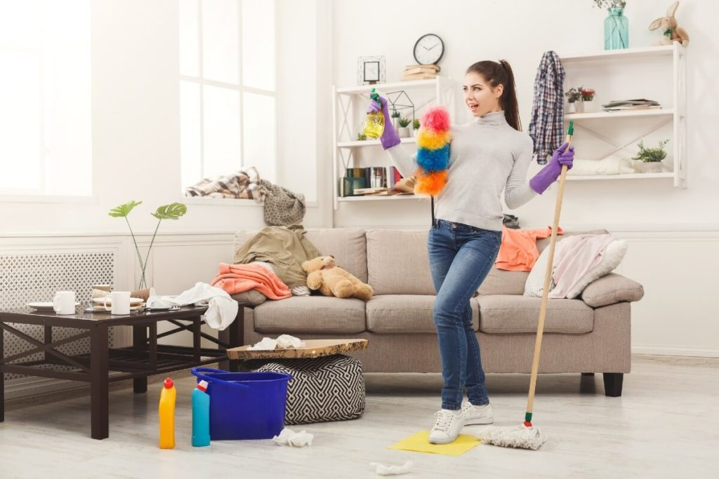 happy woman cleaning living room
