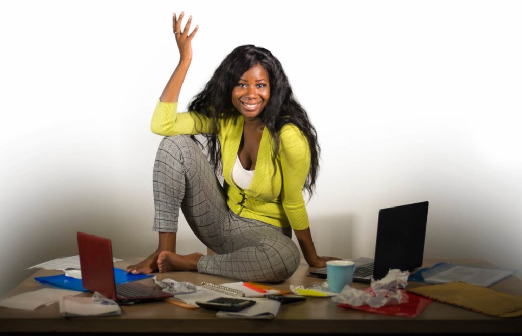 Woman sitting on a table surrounded by messy papers and laptop computers, but smiling and happy.