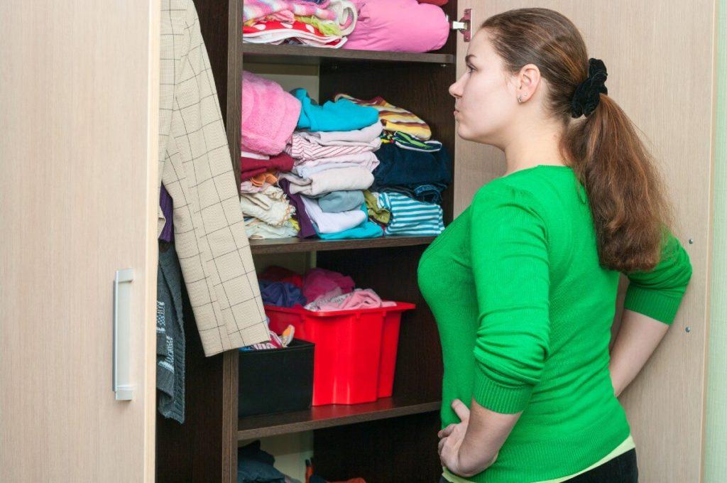 woman looking in messy wardrobe