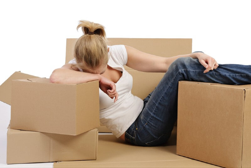 Tired woman with moving boxes