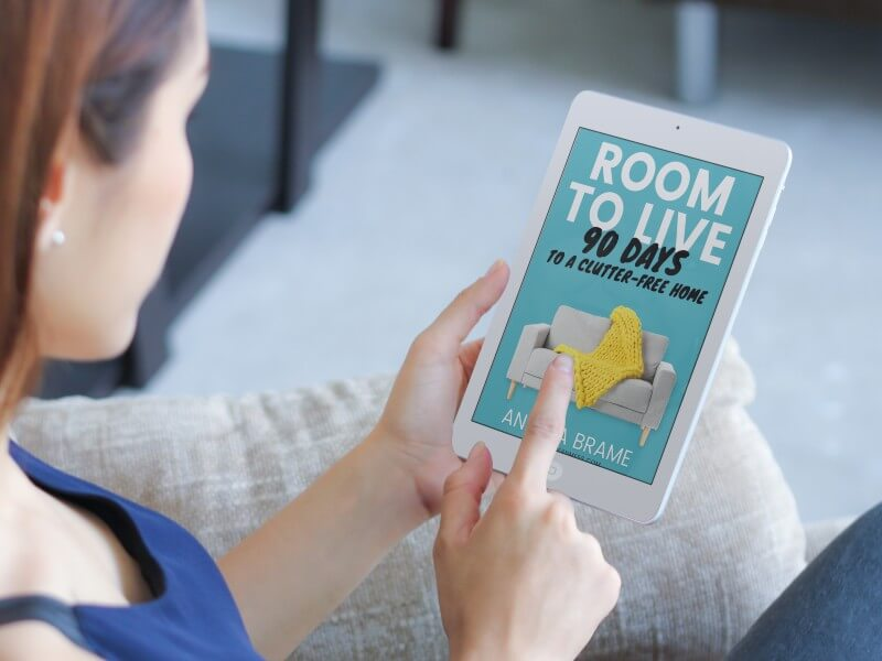 Woman reading step-by-step decluttering book ebook Room to Live on iPad mini